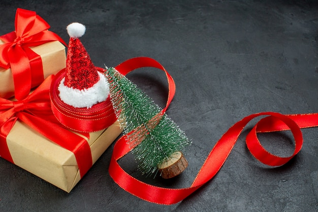 Half shot van mooie geschenken met rood lint en kerstman hoed kerstboom op donkere tafel Gratis Foto