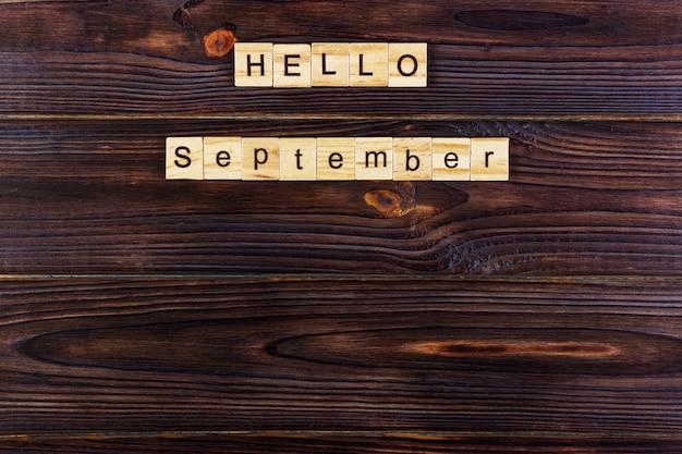 Hallo september woord. houten kubussen op houten achtergrond Premium Foto