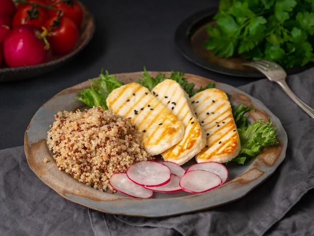 Halloumi, gegrilde kaas met quinoa, salade, radijs. Premium Foto