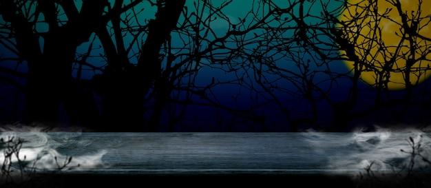 Halloween achtergrond. rook op houten tafel bij spookachtige dode boom en volle maan in blauwe gradiëntnacht Premium Foto