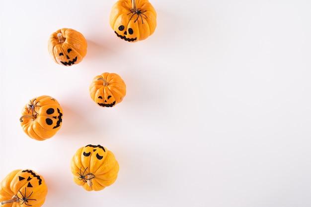 Halloween-ambachten, oranje spookpompoen op witte achtergrond met exemplaarruimte Premium Foto