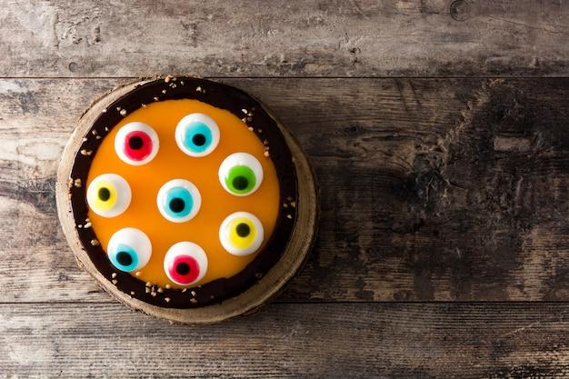 Halloween-cake met de decoratie van suikergoedogen op houten lijst. bovenaanzicht kopieer ruimte Premium Foto