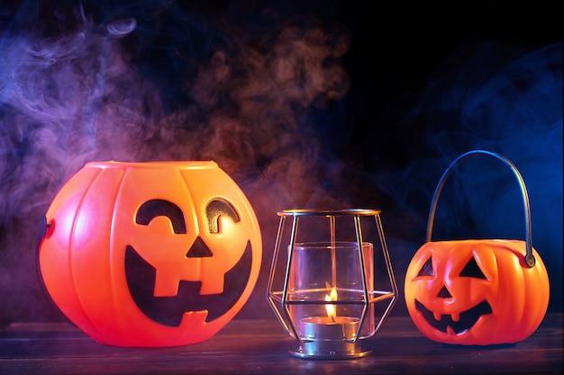 Halloween concept oranje pompoen lantaarn op een donkere houten tafel met dubbele gekleurde rook Premium Foto
