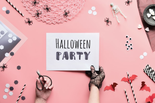 Halloween-feesttekst op witte pagina in de hand gehouden. plat leggen met zwart-witte decoraties, hand houden pagina met tekst Premium Foto