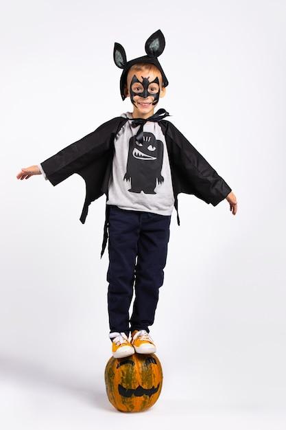 Halloween kinderkostuumfeest. jongen in halloween vleermuis kostuum zittend op een pompoen. geïsoleerd op een witte muur. Premium Foto