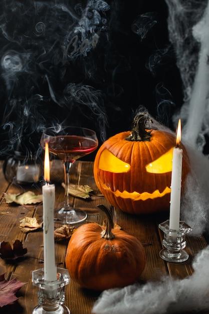 Halloween-lijst met hefboomo lantaarn, spinneweb, kaarsen en rook Premium Foto