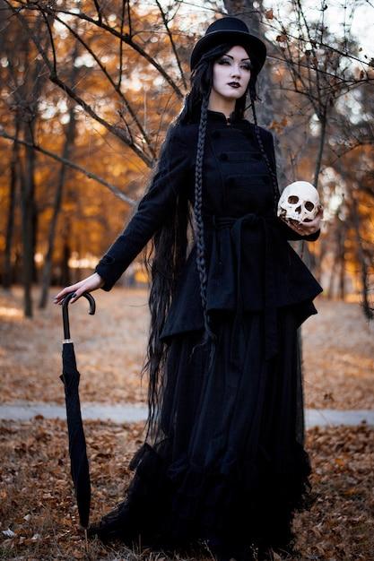 Halloween-meisje die een schedel over donkere eng houden Premium Foto