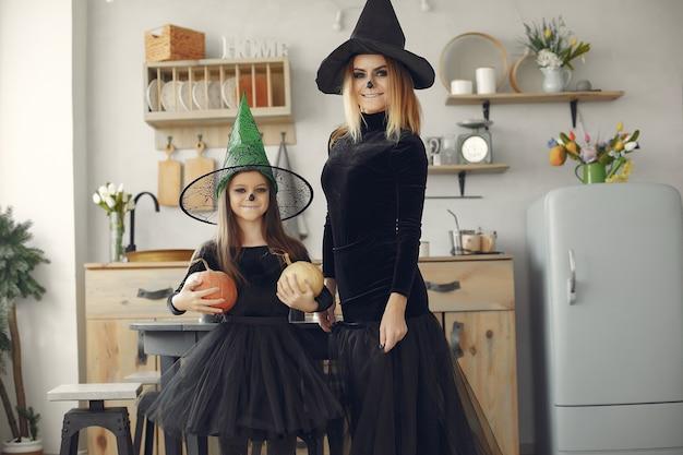 Halloween. moeder en dochter in halloween-kostuum. familie thuis. Gratis Foto
