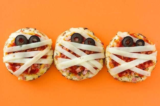 Halloween-mummies minipizza's op oranje achtergrond Premium Foto
