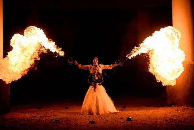 Halloween-paar die zich met vlammenwerper in handen bevinden. groot vuur Premium Foto