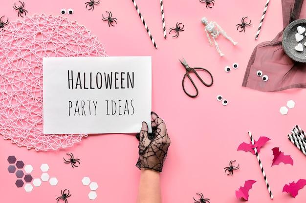Halloween plat lag met een schaar en decoraties op roze papieren achtergrond. hexagon confetti, papieren rietjes, vleermuizen en spinnen. Premium Foto