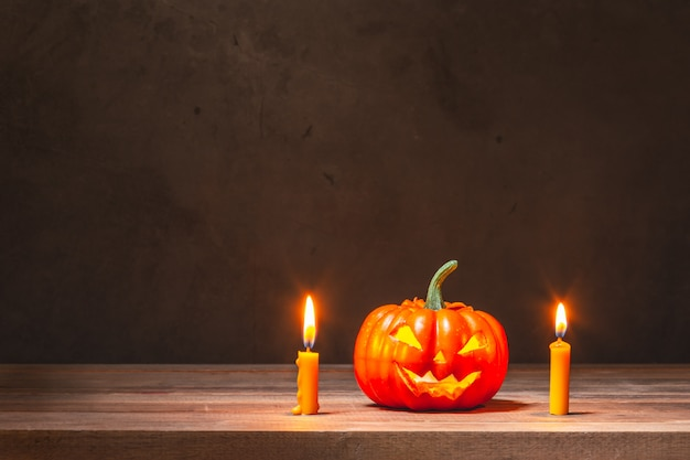 Halloween-pompoen en gele kaarsen op houten lijst Premium Foto