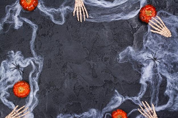 Halloween-vakantie met skelettenhanden, pompoenen, spinnen en spinneweb op zwart Premium Foto