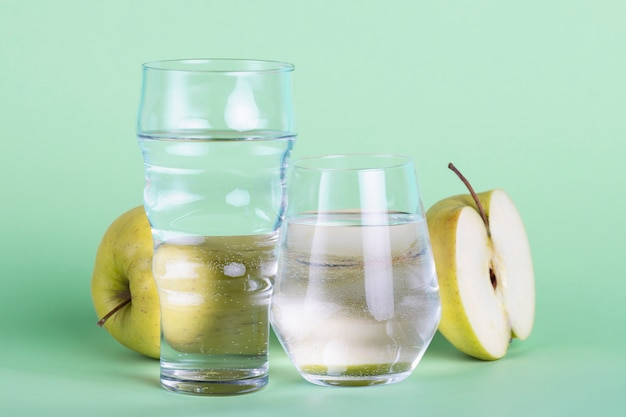Halve appel en waterglazen op groene achtergrond Gratis Foto