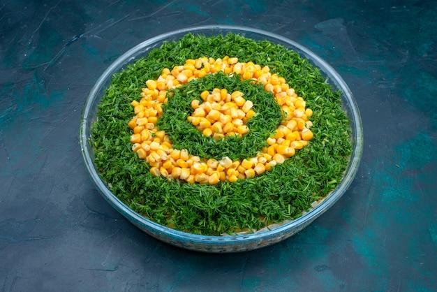 Halve bovenaanzicht greens salade met likdoorns binnen ronde glazen plaat op donkerblauwe achtergrond. Gratis Foto