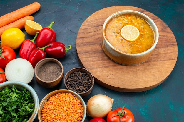 Halve bovenaanzicht groentesoep met verse groenten greens en kruiden op donkerblauw bureau. Gratis Foto
