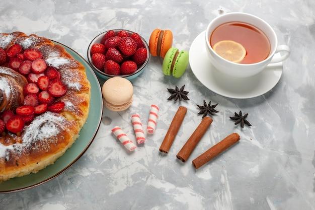 Halve bovenaanzicht kopje thee met franse macarons en taart op licht-wit oppervlak Gratis Foto
