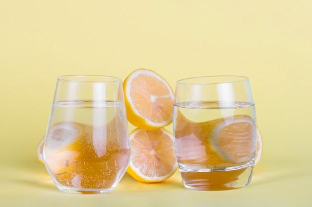 Halve citroenen en waterglazen op gele achtergrond Gratis Foto