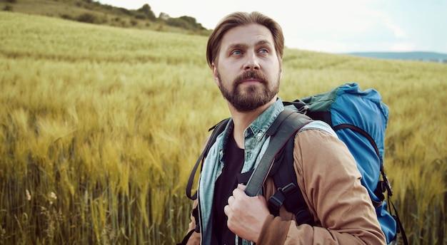 Halve draai portret van bebaarde backpacker wandelen in het landschap bewonderen landschap Premium Foto