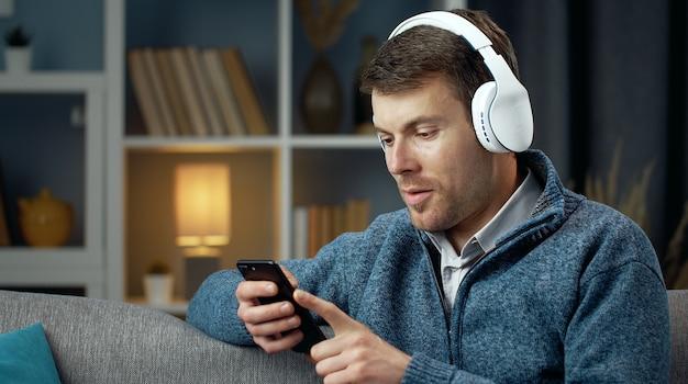 Halve draai portret van casual blije man met behulp van smartphone en draadloze koptelefoon zittend op de bank Premium Foto