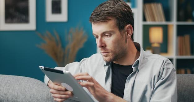 Halve draai portret van casual jongeman met behulp van tablet scherm zittend op de bank aan te raken Premium Foto