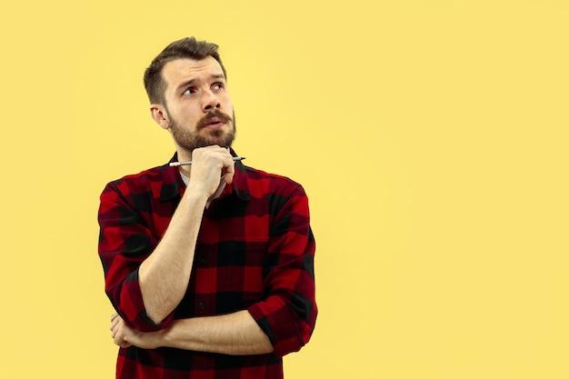 Halve lengte close-up portret van een jonge man in shirt op gele ruimte. de menselijke emoties, gezichtsuitdrukking concept. vooraanzicht. trendy kleuren. negatieve ruimte Gratis Foto