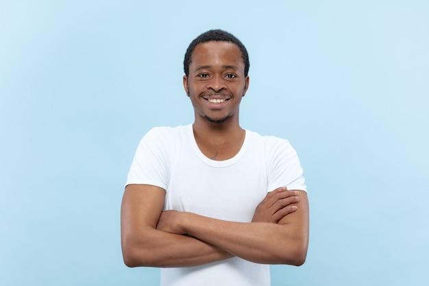 Halve lengte close-up portret van jonge afro-amerikaanse man in wit overhemd op blauwe ruimte Gratis Foto