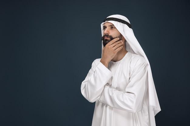 Halve lengte portret van arabische saoedische zakenman. jong mannelijk model staat en ziet er attent uit. concept van zaken, financiën, gezichtsuitdrukking, menselijke emoties. Gratis Foto