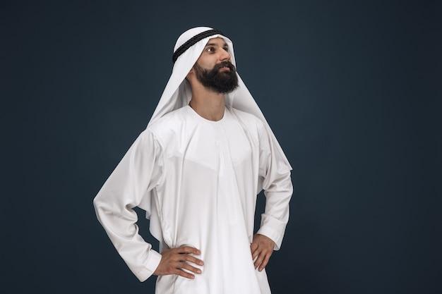Halve lengte portret van arabische saoedische zakenman op donkerblauwe studioachtergrond. jonge mannelijke model staan en glimlachen. concept van zaken, financiën, gezichtsuitdrukking, menselijke emoties. Gratis Foto