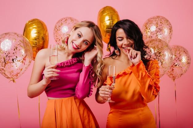 Halve lengte portret van twee jonge dames die champagne drinken Gratis Foto