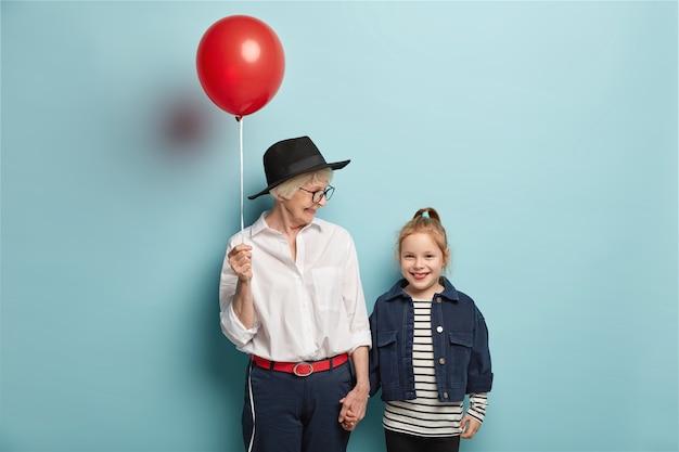 Halve lengte shot van aanhankelijke oma feliciteert klein kind met de eerste dag op school, houdt rode ballon met blije uitdrukkingen. vrolijke oma, kleindochter komt in een goed humeur terug van circusvoorstelling Gratis Foto