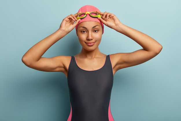 Halve lengte shot van bekwame professionele zwemmer past bril aan, draagt zwemkleding, badmuts Gratis Foto