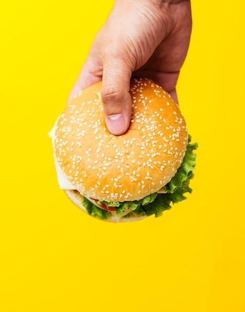 Hamburger die over gele achtergrond wordt gehouden Premium Foto