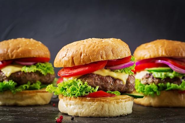Hamburger drie met de hamburger van het rundvleesvlees en verse groenten op donkere achtergrond. Premium Foto