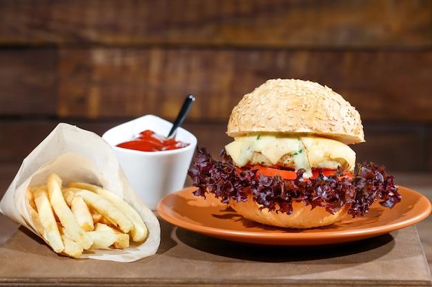 Hamburger en frieten op de houten tafel Premium Foto