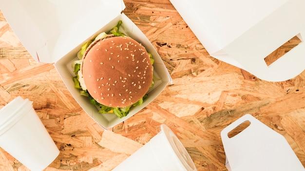 Hamburger in de doos met pakketten op houten achtergrond Gratis Foto
