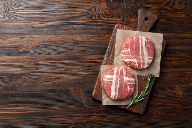 Hamburger ruwe koteletten met rozemarijn op snijplank en houten tafel Premium Foto