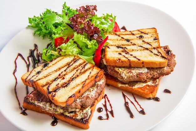 Hamburgerclose-up met bacon en kaassaus, salade, olijvenvulling Gratis Foto
