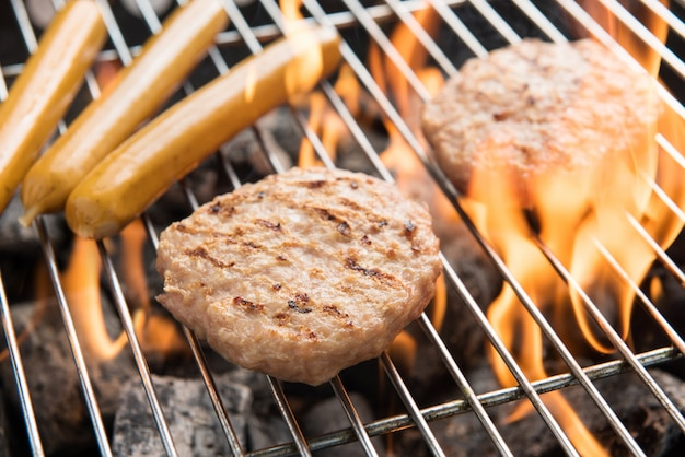Hamburgers en worstjes koken op vlammen bij de grill. Premium Foto