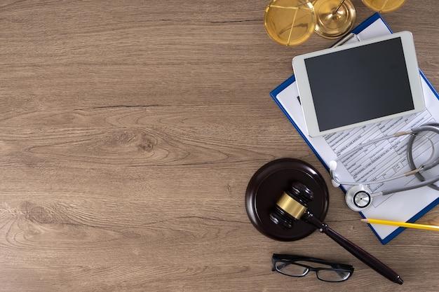 Hamer, bril, rapport, stethoscoop, weegschaal en tablet Premium Foto