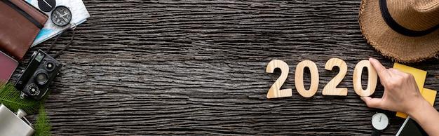 Hand 2020 gelukkig nieuwjaar nummer op houten tafel met avontuur accessoire item banner Premium Foto