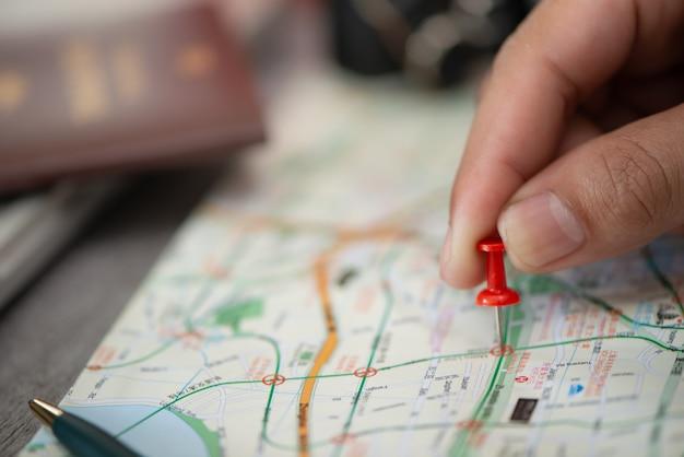 Hand bij het richten van rood speldplan om op kaart te reizen, reisconcept Premium Foto