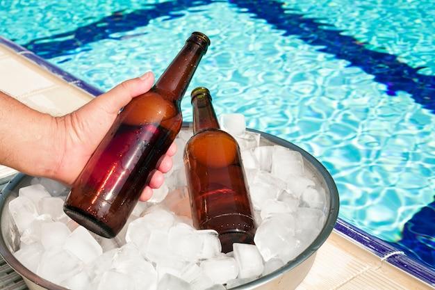 Hand die bierfles neemt uit dienblad met ijs Gratis Foto