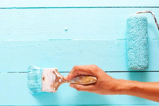 Hand die blauwe kleur op witte houten plank schildert Premium Foto