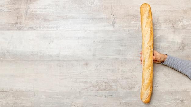Hand die een broodtoverstokje met exemplaarruimte houdt Gratis Foto