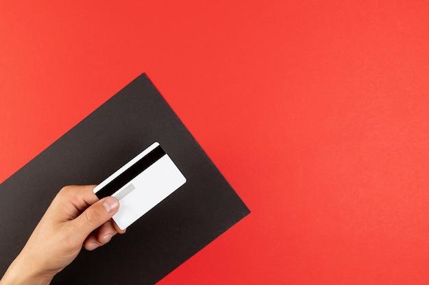 Hand die een creditcard op rode achtergrond houdt Gratis Foto