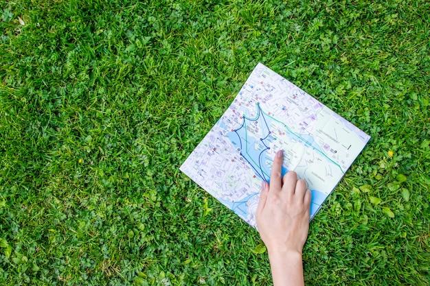 Hand die een document blad met de reiskaart houdt over groene bosaardachtergrond. Premium Foto