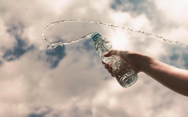 Hand die een duidelijke plastic fles zuiver drinkwater verfrist en plons houdt Premium Foto