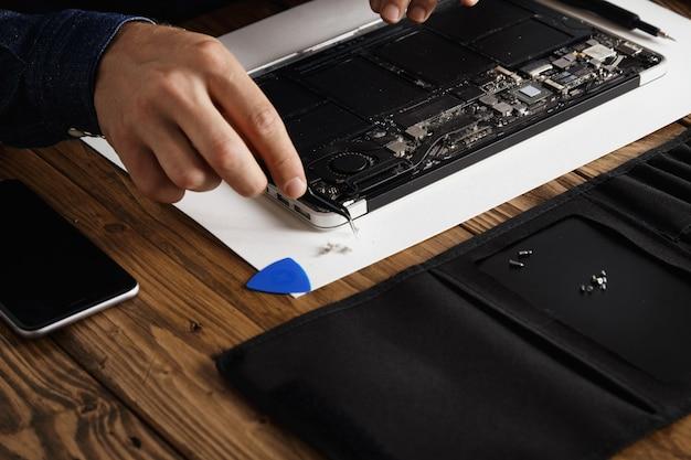 Hand die een gebogen esd-pincet gebruikt om stof te verwijderen van elektronische kaarten van kapotte, dunne computerlaptops om deze te repareren en weer aan het werk te krijgen. Gratis Foto