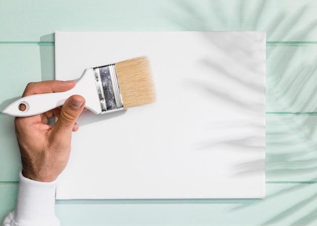Hand die een het schilderen borstel en een schaduw van bladeren houdt Gratis Foto